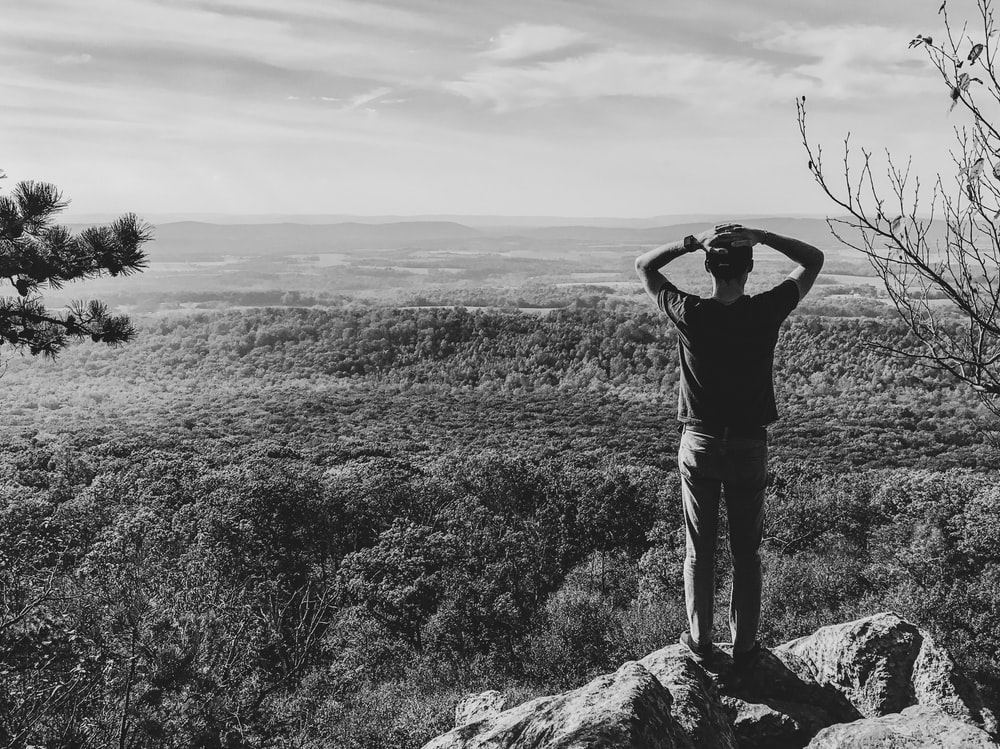 grayscale photography of man standing on rock