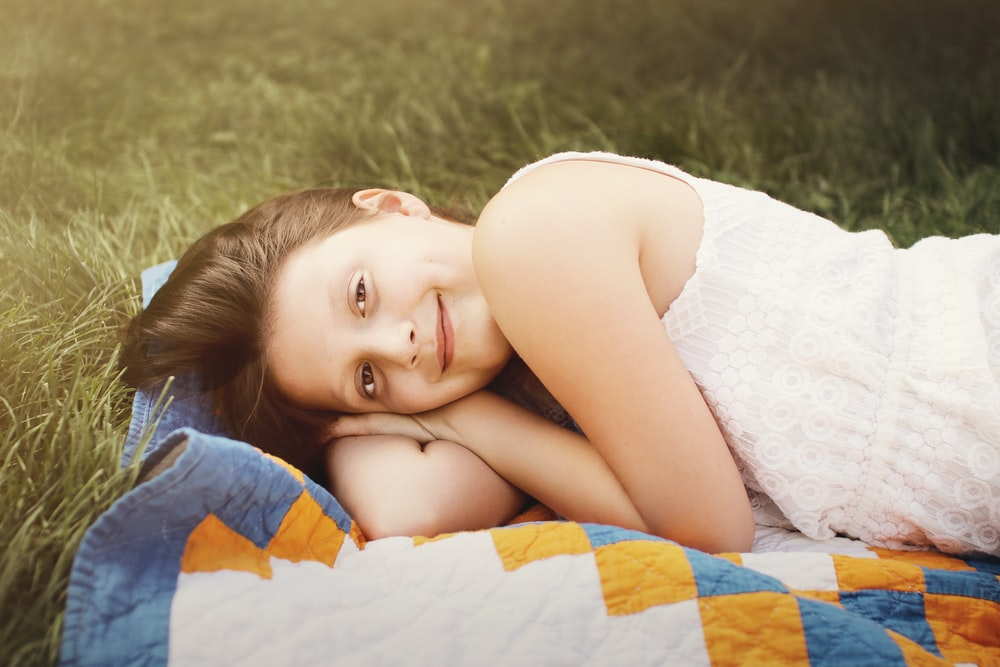 girl lies on textile on grass