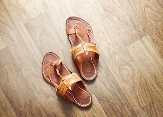 pair of brown T-strap sandals on floor