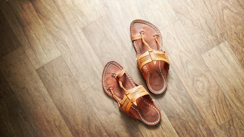 pair of brown T-strap sandals on floor