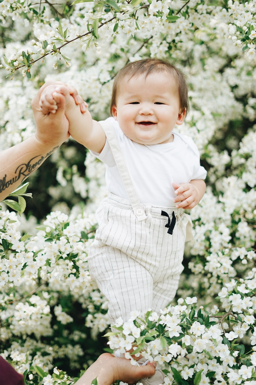 baby near white petaled flowers