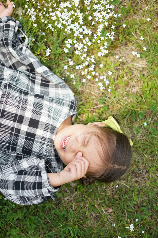 girl lying on grass field