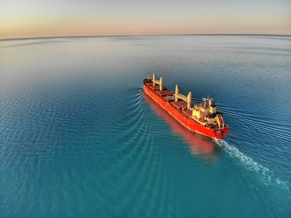 red and white cargo ship at middle of ocean