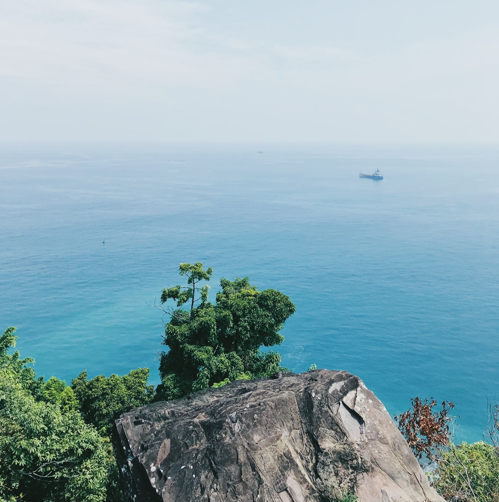 aerial photography of cliff viewing blue sea during daytime