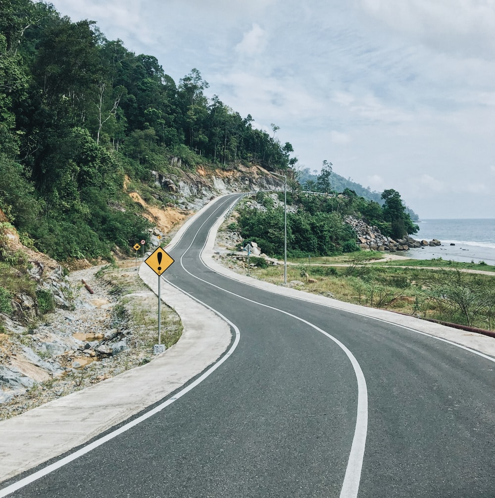 gray concrete road with no vehicle viewing blue sea during daytime