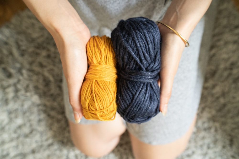 person holding yellow and black yarns
