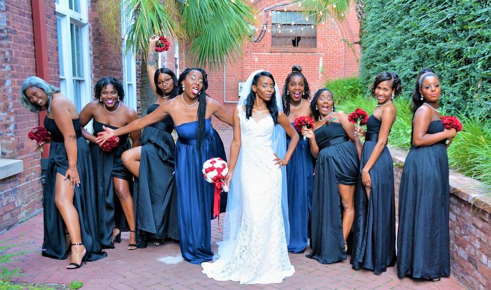 bride between women wearing black dress during daytime