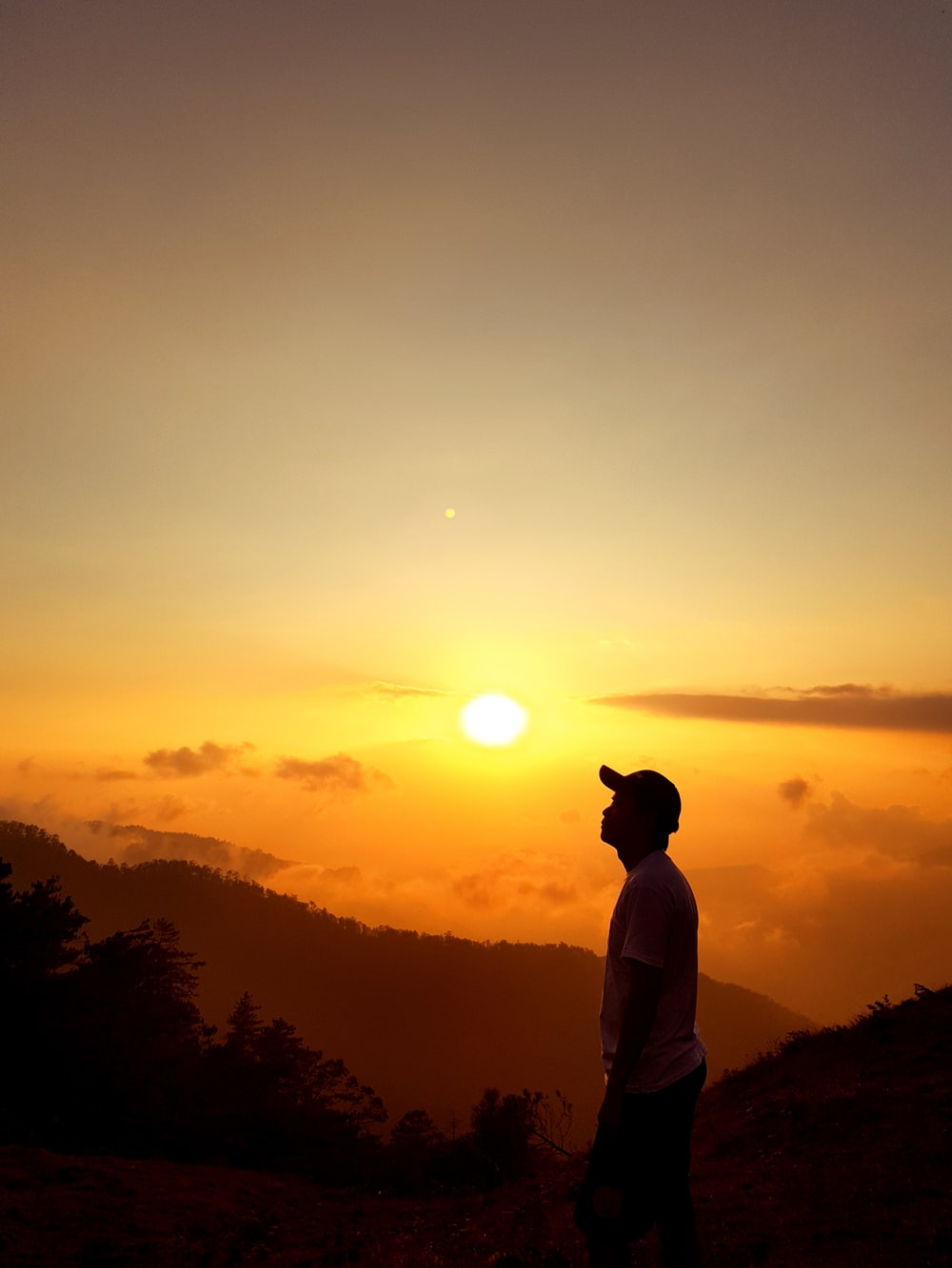 man standing on top of mountain during golden hour