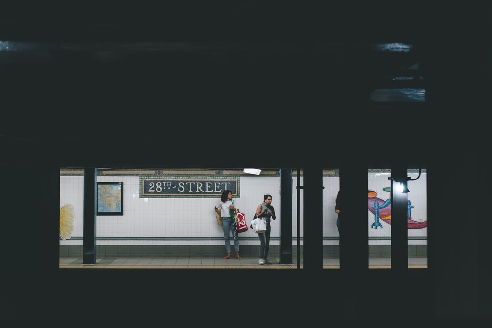 two women standing on train station