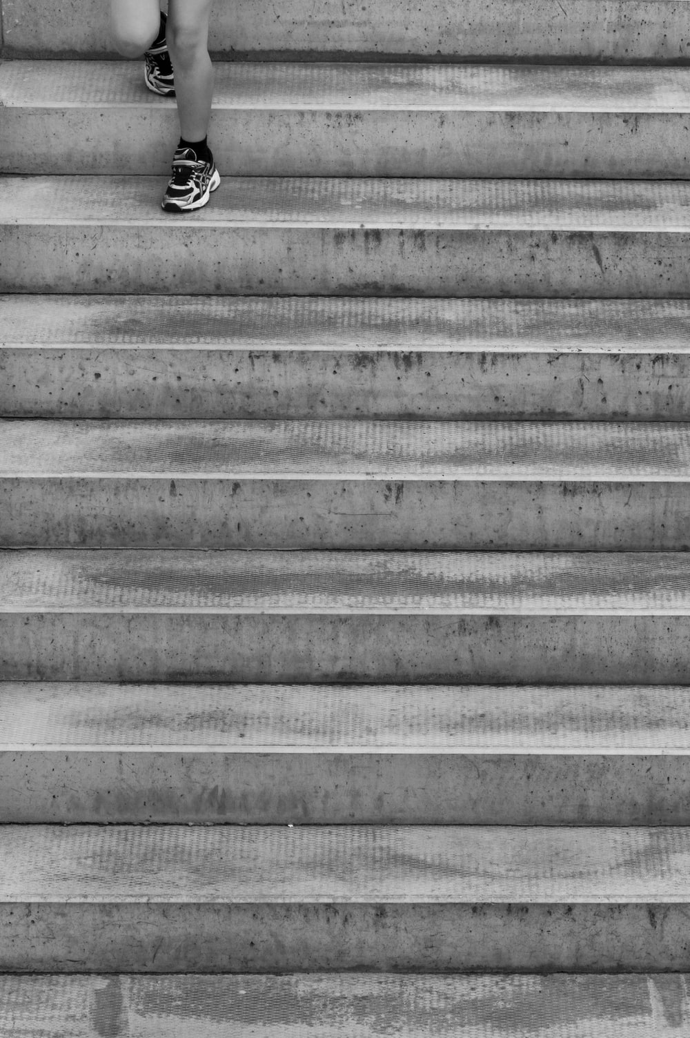 grayscale photo of person's foot on staircase