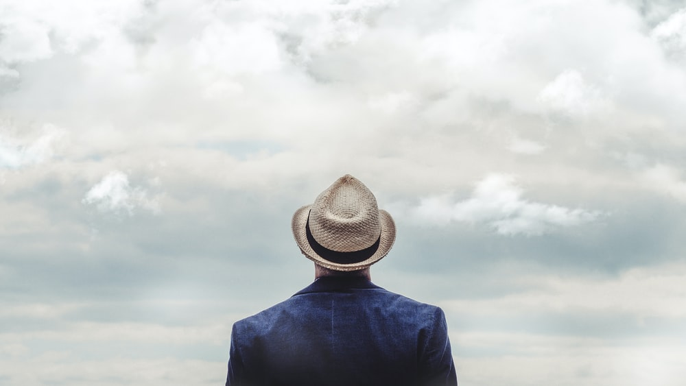 man standing under cloudy sky during daytime