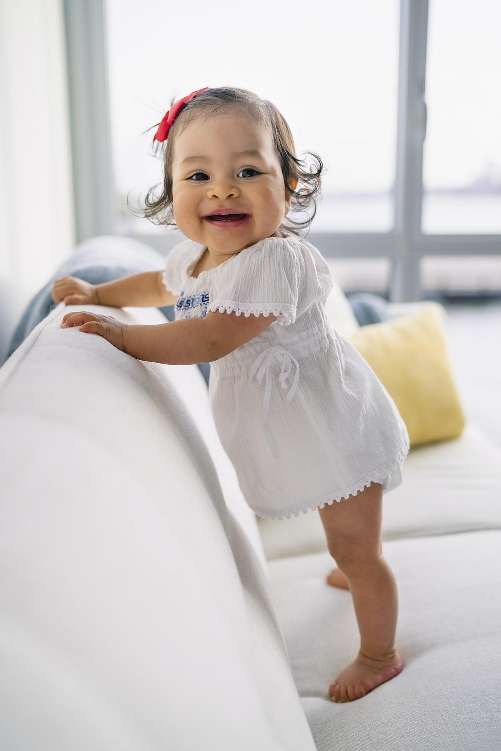smiling toddler girl standing on sofa