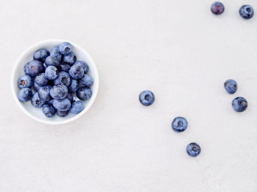 blueberries in bowl and white surface