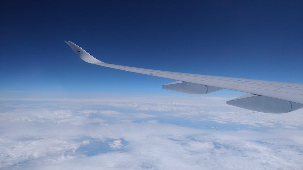 flying gray airplane during daytime