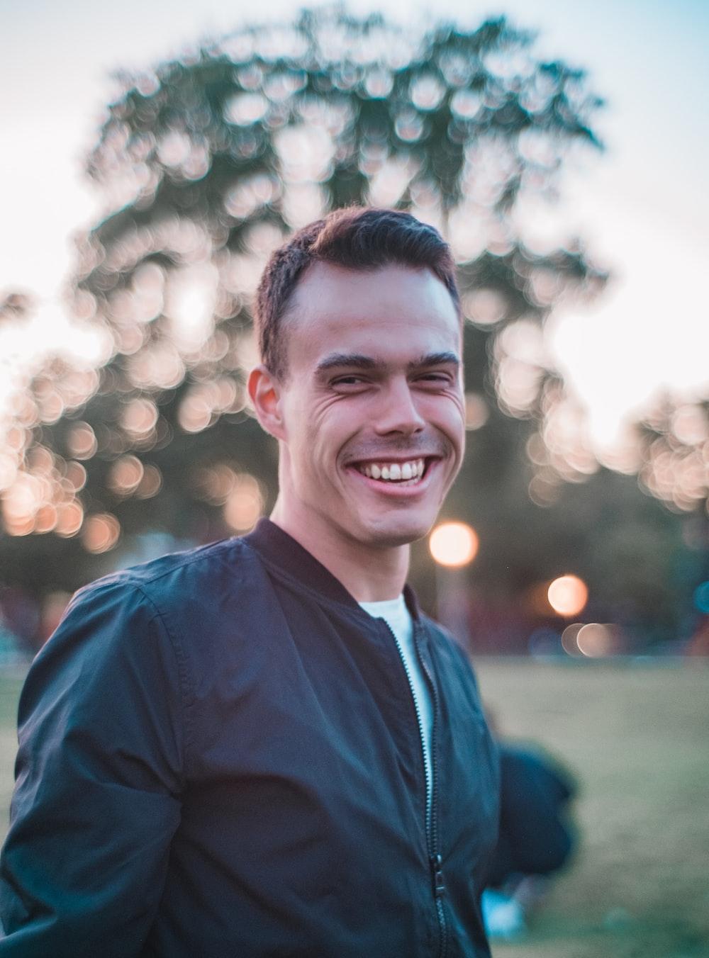 man in black top taking selfie outdoors