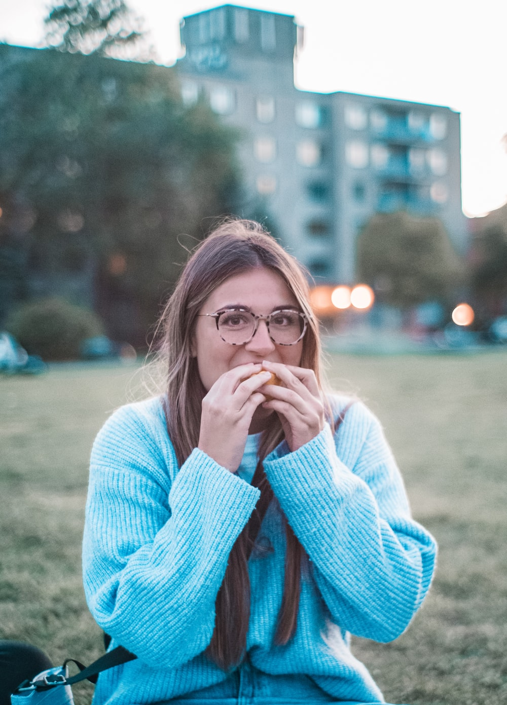 woman in blue sweater eating outdoors