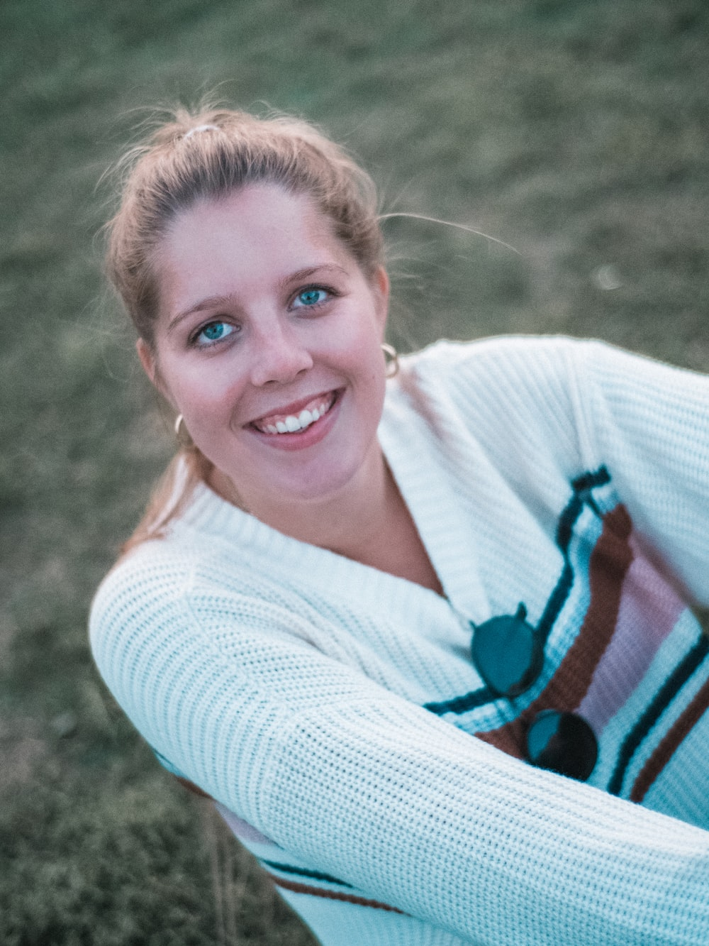 smiling woman wearing white V-neck sweater