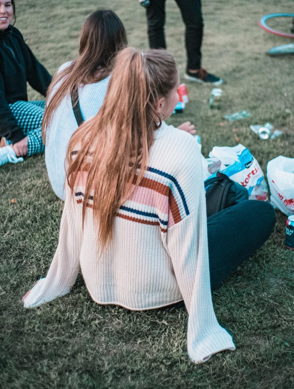 three women sitting on green grass field