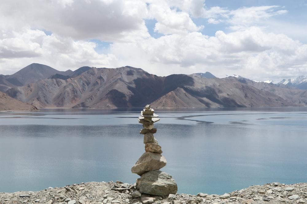 gray balance stones near body of water during daytime