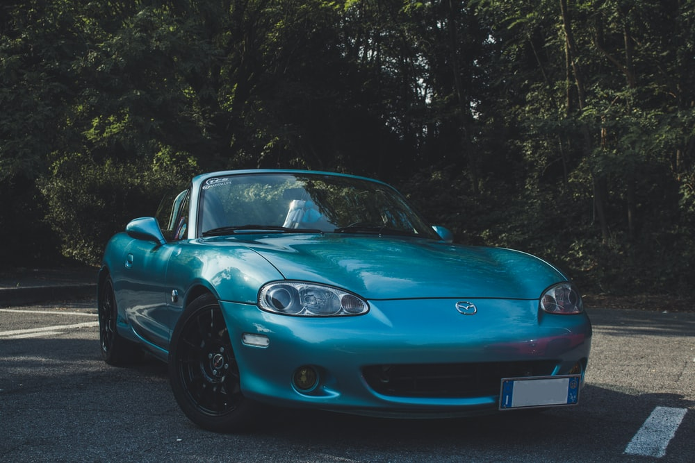 blue Mazda convertible coupe on road