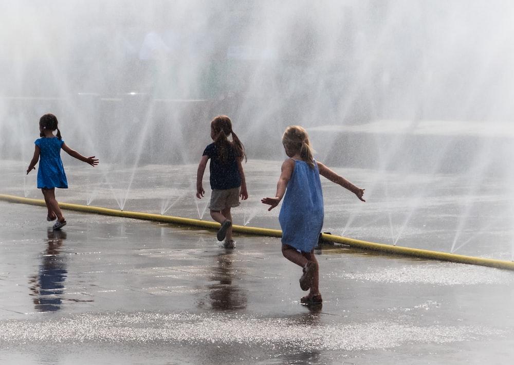 three girls running beside water fountains