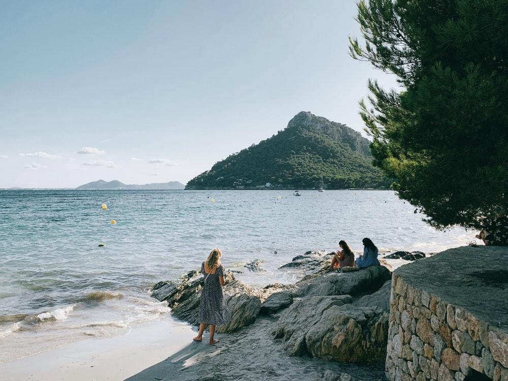 three women siting on rock formation near sea