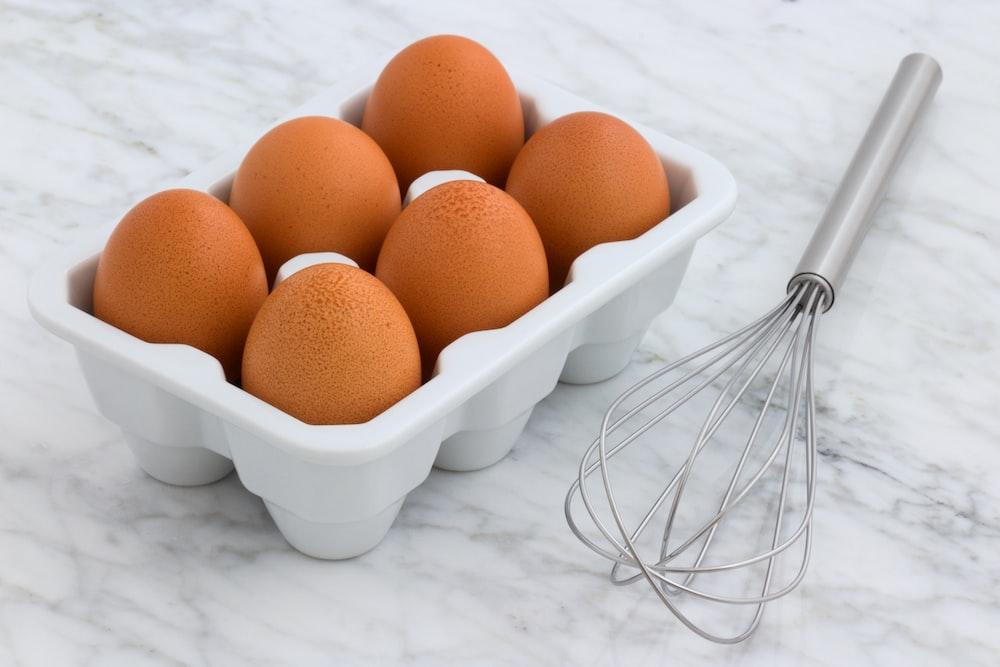 pack of organic eggs beside silver whisk