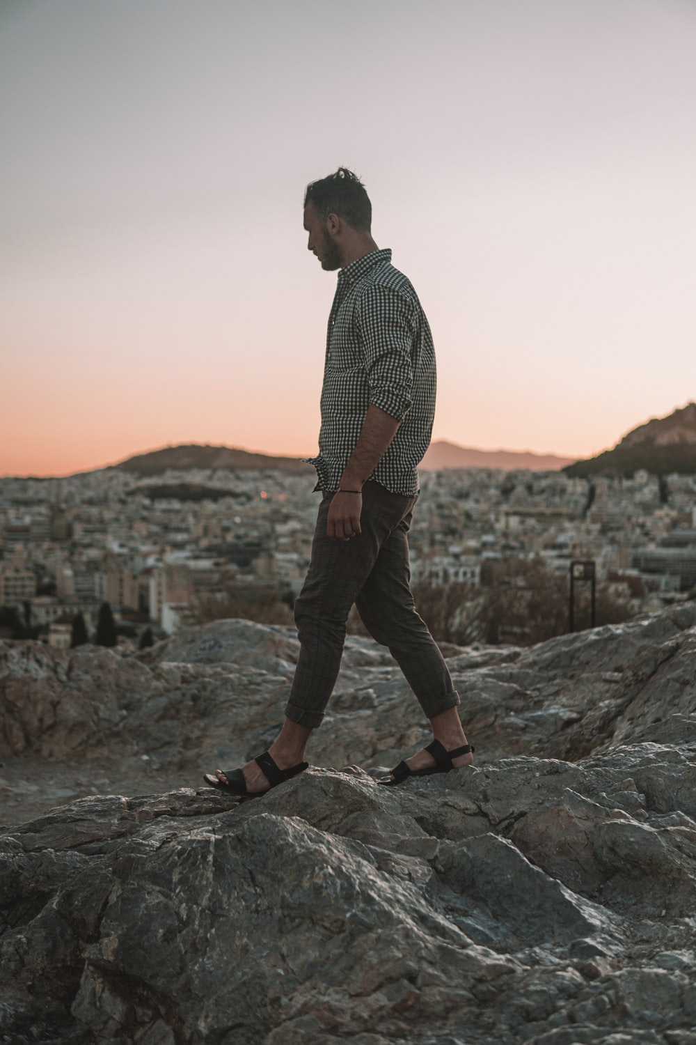man walking on the rocky field photography
