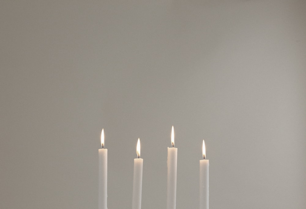 four lighted white candles