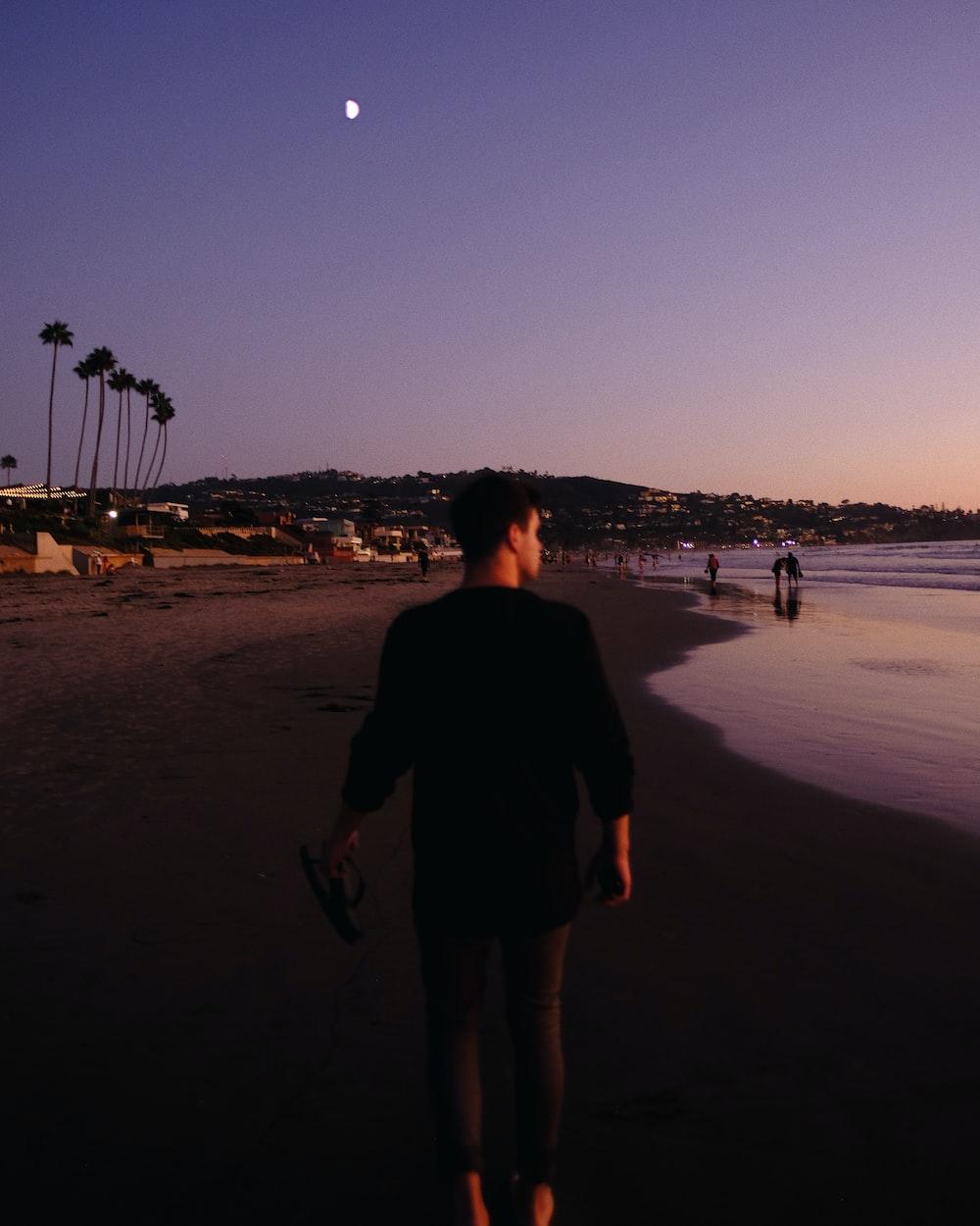 man walking along black sand beach shore