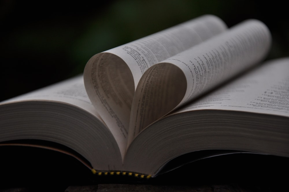 two folded book pages forming heart