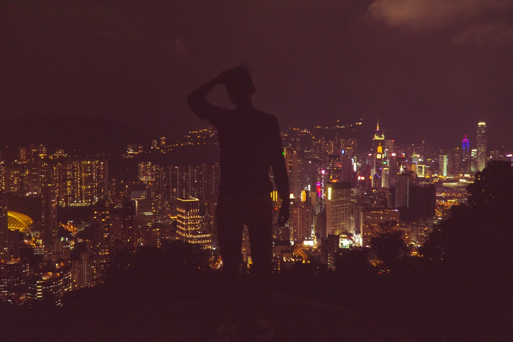 silhouette photography of man overlooking urban city