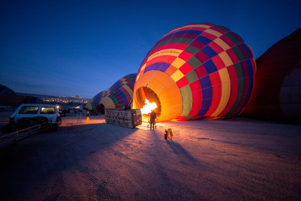 person standing near multicolored hot air balloon during night time