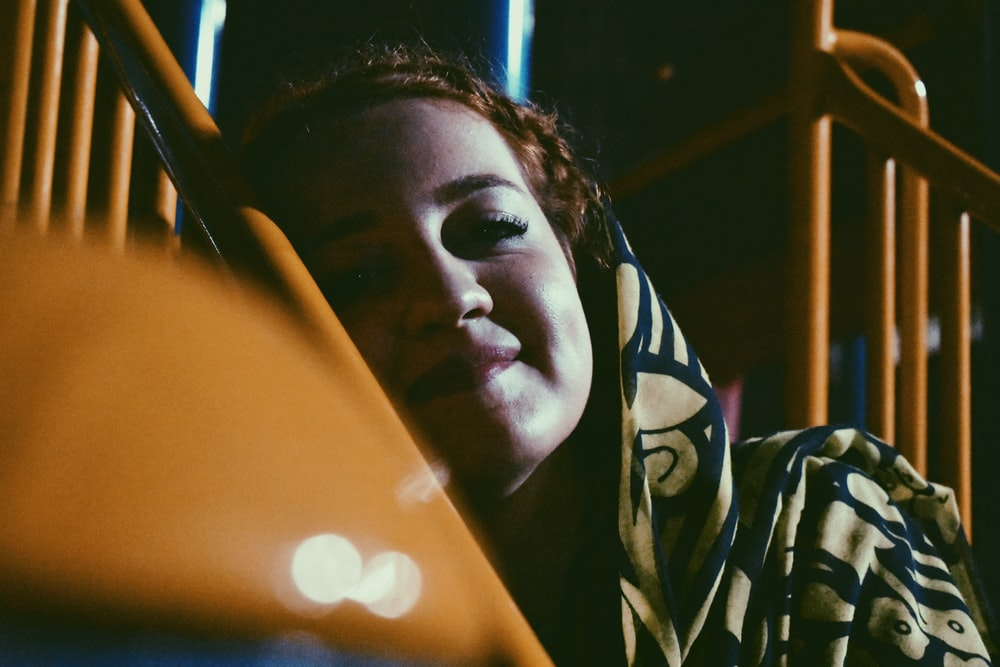 woman leaning on yellow metal railings