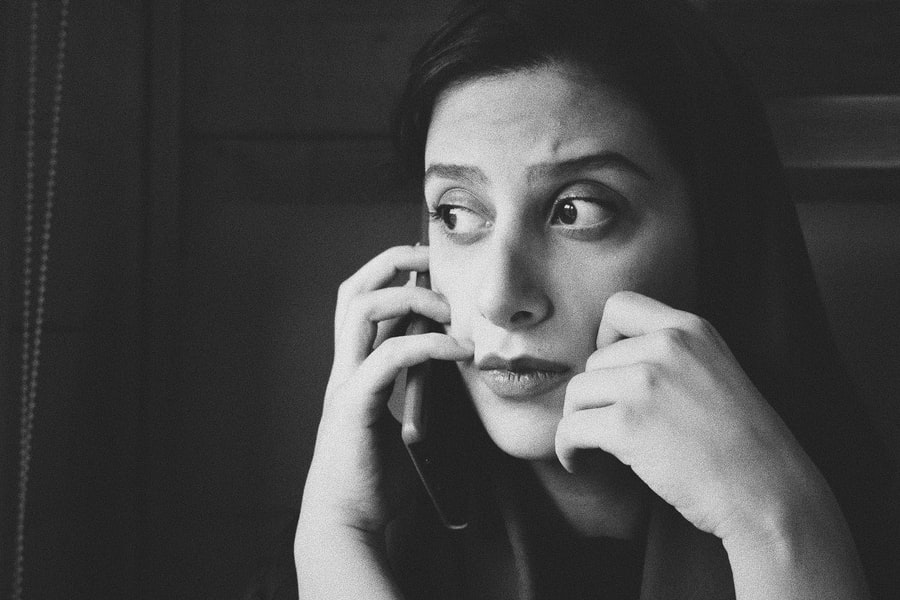 A woman with a concerned expression is talking on her cell phone and looking into the distance.
