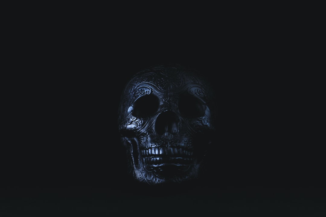 Black sugar skull on black background.