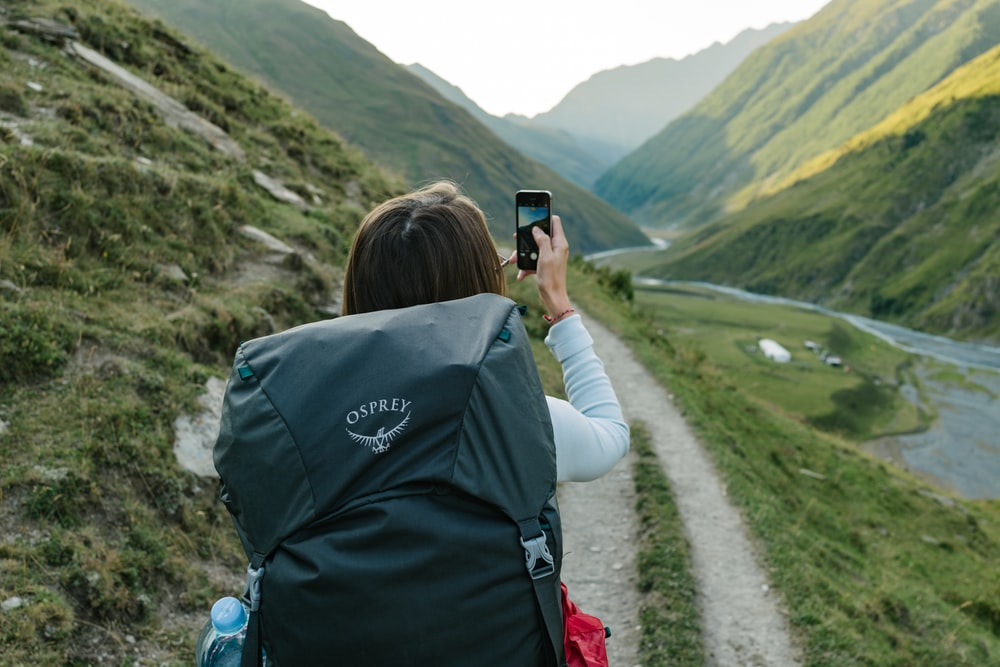 woman walking near dirt road between mountain range during daytime