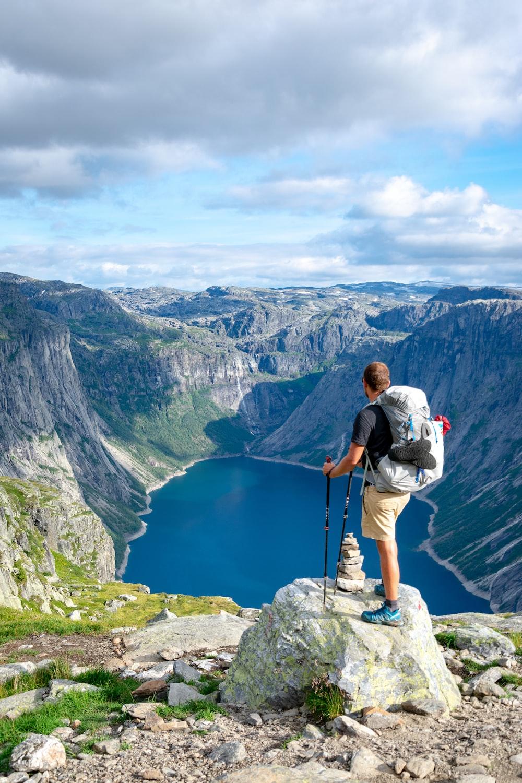 man standing on rock looking towards lake