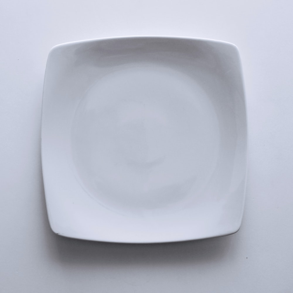 empty ceramic plate on white textile