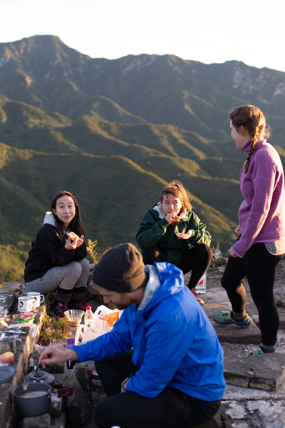 three woman and one man eating on top hill during daytime