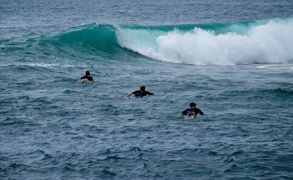 three men playing surfboarding during daytime