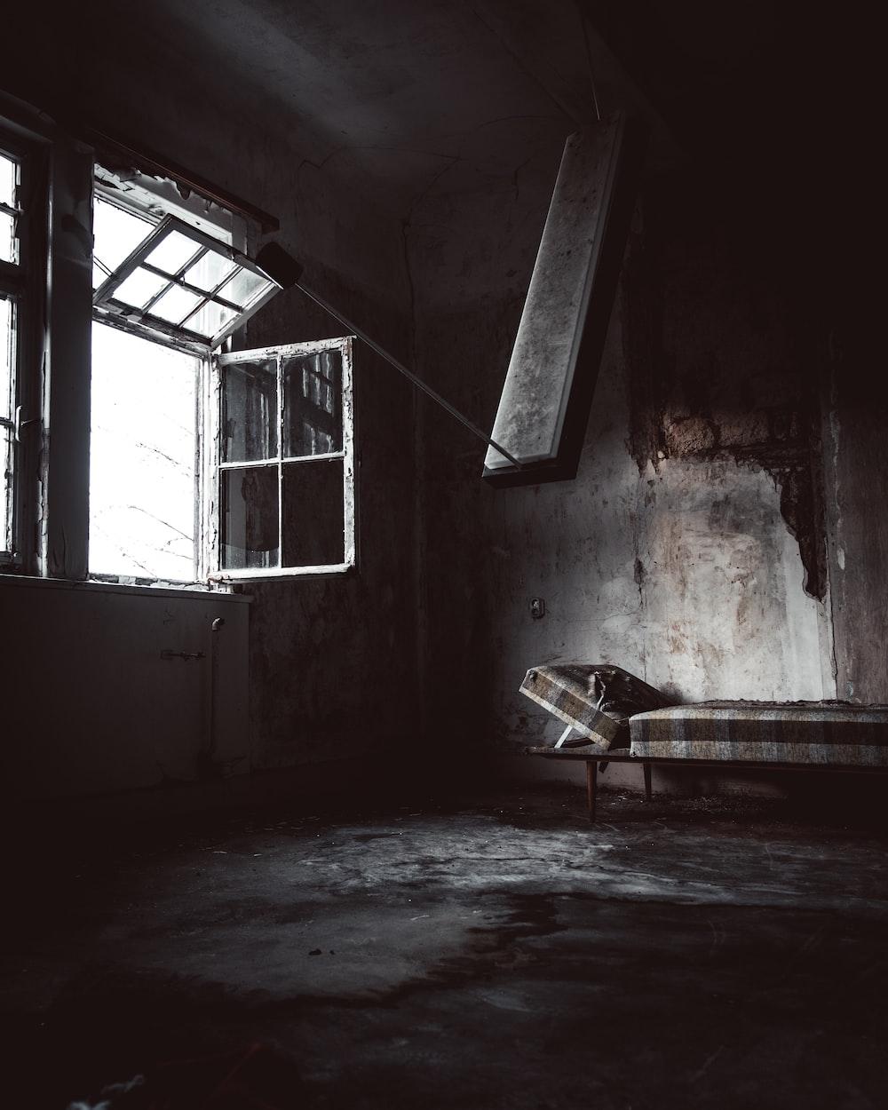 bed inside abandoned building near opened window