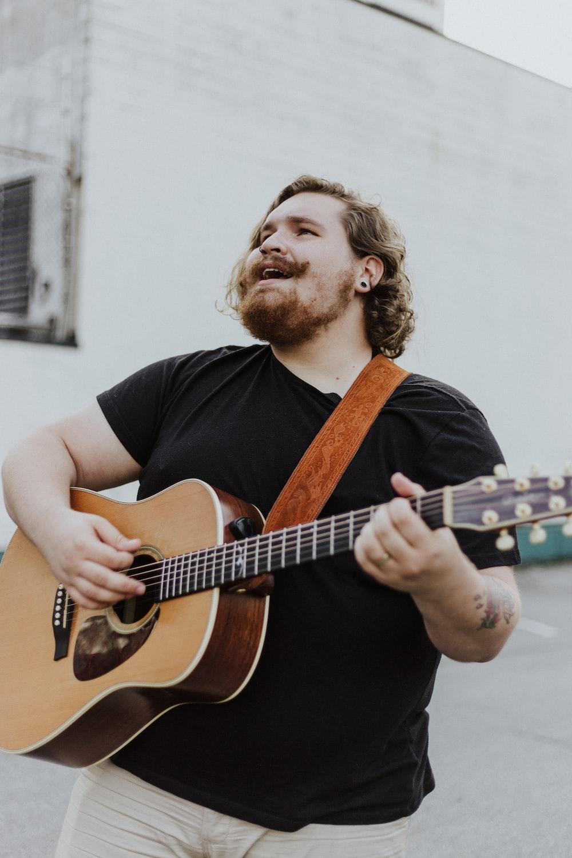 man wearing black shirt playing acoustic guitar