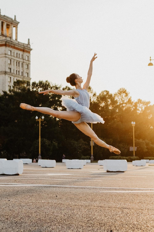girl wearing gray dress dancing during daytime