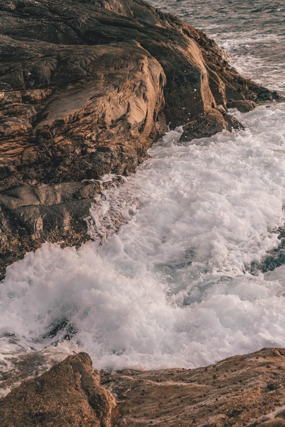 sea wave crashing on rock boulders
