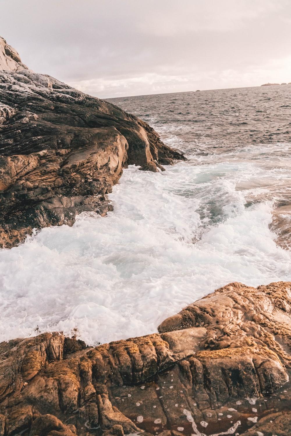 waves crashing on rock boulders