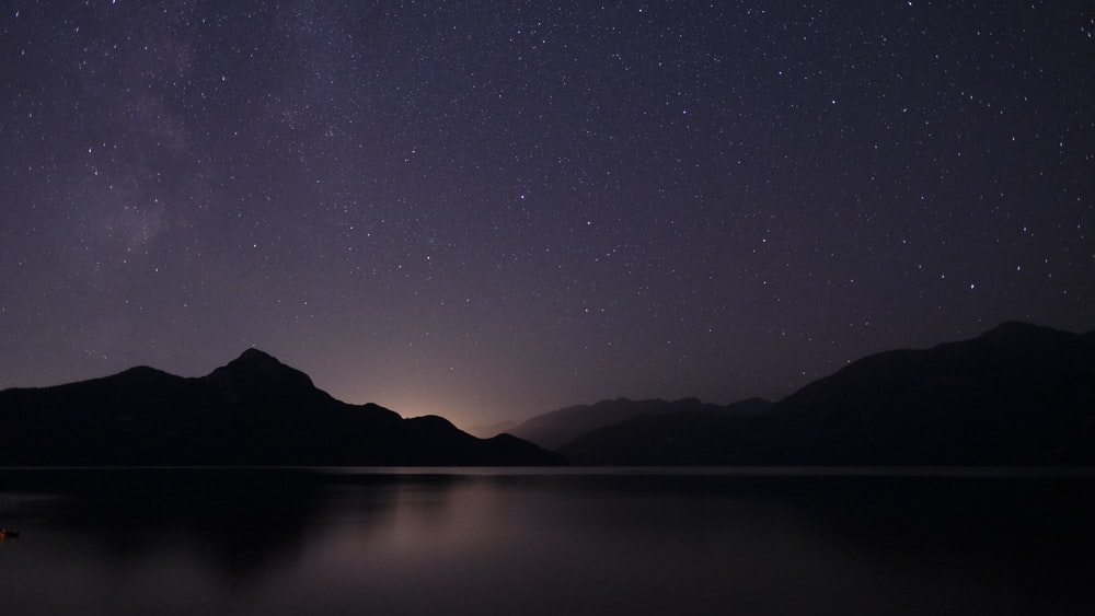 body of water across mountain during nighttime