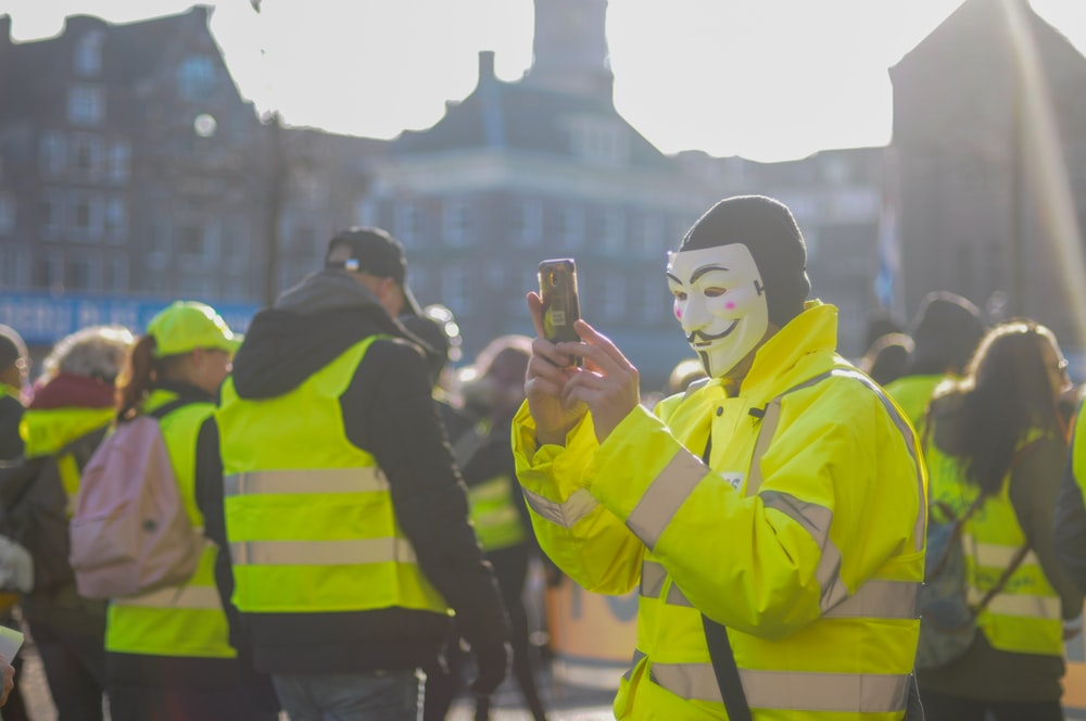 person wearing guy fawkes mask using phone surrounded with people