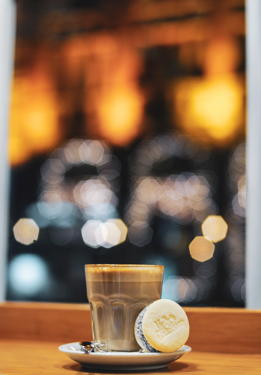 clear drinking glass beside macaroon