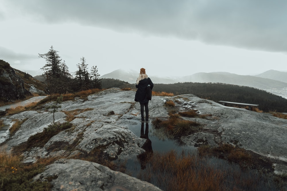 woman standing on puddle of water on mountain top